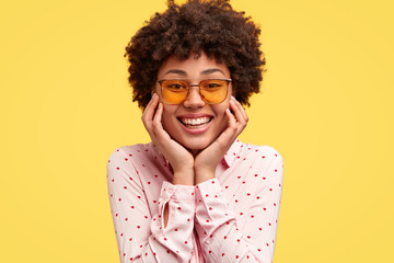 Portrait of happy black young woman has pleasant toothy tender smile, holds chin, looks joyfully at you, wears trendy sunglasses and fashionable blouse, models in studio against yellow background.