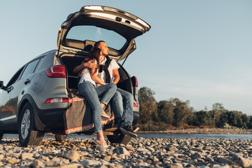 Happy Couple on Roadtrip into the Sunset in SUV Car Wall mural