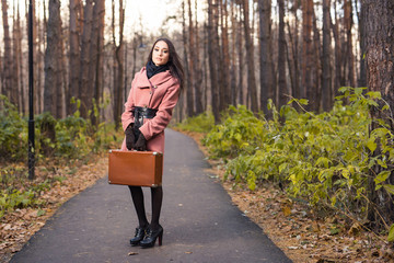 People, season and fashion concept - Brunette woman with retro suitcase in the autumn park.