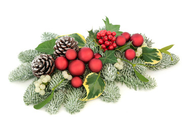 Christmas table decoration with red bauble decorations, holly berries, snow covered spruce pine, ivy, pine cones and mistletoe isolated on white background.