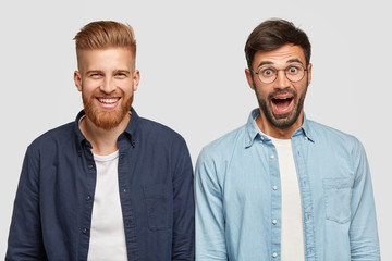 Isolated shot of two joyful surprised bearded guys express positive emotions, rejoice promotion for good diligent work, recieve money reward, collaborate together, pose in studio, smile broadly