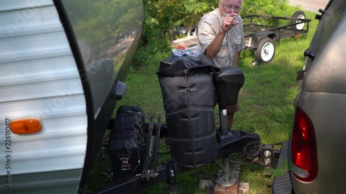 Elderly man puts the window up on his pickup truck so the