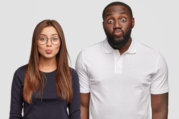 Horizontal view of pleasant looking interracial male and female keep lips round, going to kiss somebody, make grimace at camera, pose against white background. Multiethnic friendship concept.