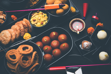 Diwali sweets and snacks arranged in a group with Diya or oil lamp, flowers and Fire Crackers or Patakhe over moody background, selective focus