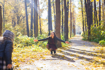 People, family and leisure concept - young mother have fun with her daughter in autumn park