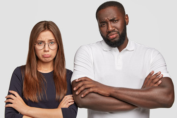Horizontal shot of displeased young multiethnic couple have miserable looks as draw distrubing picture in imagination, keep arms folded, doesnt like something, isolated over white background