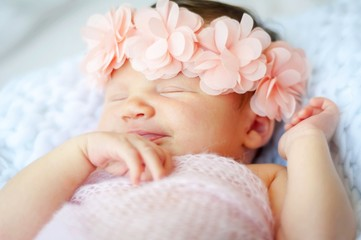 Cute and adorable Caucasian newborn baby girl with a pink flower head band smiling in her sleep.