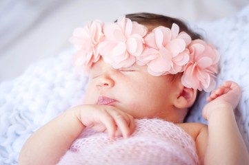 Sweet newborn Caucasian baby sleeping. Pink flower head band. New born child photo session.