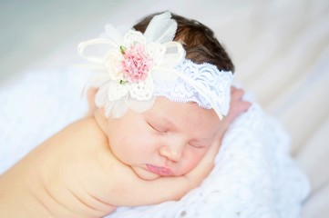 Sweet and innocent Caucasian infant girl sleeping on a soft blanket, flower head band on her head.