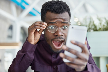 Shocked dark skinned young man stares with bugged eyes, keeps jaw dropped, wears transparent glasses, recieves unexpected message on cell phone, dressed in formal purple shirt, poses indoor.