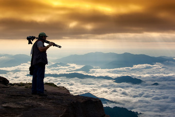 Silhouette of Man photographer with tripod and camera standing on top of mountain looking beautiful scene for taking photo of sunset mountain Travel Lifestyle hobby concept adventure  vacation outdoor