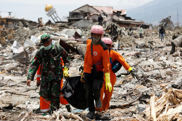 Rescue workers and a soldier remove a victim of last week's earthquake in the Balaroa neighbourhood in Palu, Central Sulawesi