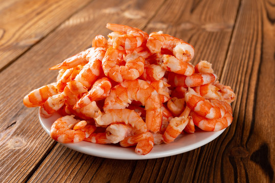 side view studio shot of peeled shrimps on a dish