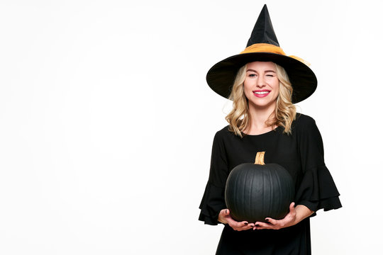 Halloween Witch holding large black pumpkin winking. Beautiful young woman in witches hat and costume holding pumpkin over white background.