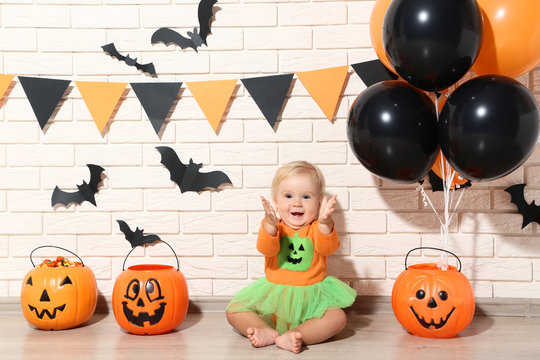 Baby girl in halloween costume with pumpkin buckets and balloons