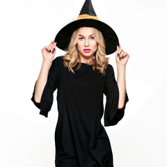Sensual Halloween Witch Studio Portrait. Attractive young woman dressed in witch halloween costume isolated over white background.
