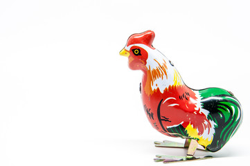 Antique tin toy rooster isolated on white background