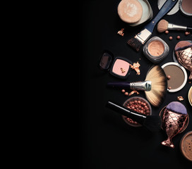luxery Set of bronze powder with makeup brushes on black background