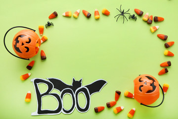 Halloween candy corns and pumpkin bucket on green background