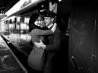 Vintage couple embracing and laughing on railway station platform as train arrives