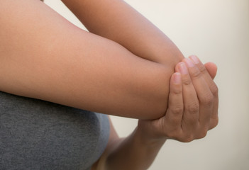 Close up woman's hand holding her elbow . Elbow pain concept.
