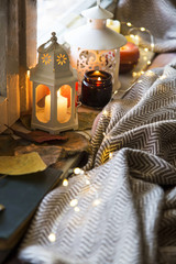 Cozy festive autumn decor still life, fall still life candles and lanterns at window with lights and blanket