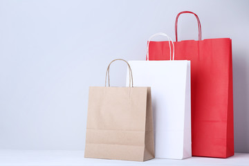 Colorful paper shopping bags on grey background