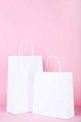 White paper shopping bags on pink background