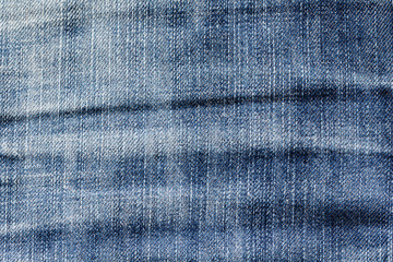 texture of dark blue denim with pleats and scuffed as a background