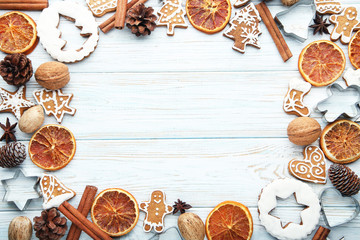 Christmas gingerbread cookies with dry oranges and walnuts on white wooden table