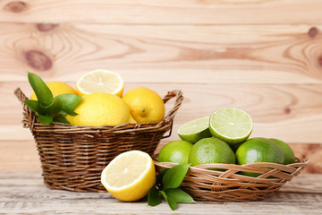 Lemons and limes with green leafs in baskets on wooden table