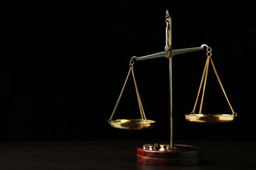 Scales of justice on wooden table