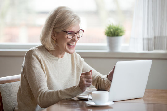 Happy mature middle aged elderly business woman winner excited by reading good news looking at laptop, glad senior older lady watching celebrating online bid bet win or great result victory concept