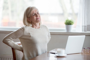 Upset mature middle aged woman feels back pain massaging aching muscles, sad senior older lady suffers from low-back lumbar pain sitting in incorrect sedentary posture, backache radiculitis concept