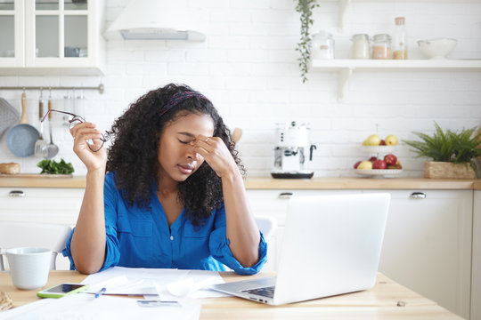 Sad depressed young mixed race female sitting at kitchen table with papers and laptop, having tired worried look, massaging eyes while calculating family budget, stressed with financial problems