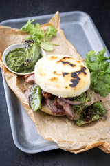 Traditional Columbian arepa con carne desmechada with shredded beef steak and aji criollo as closeup on a backing paper