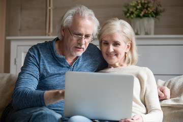 Retired couple using laptop together sitting on sofa, smiling senior middle aged man and woman read internet news talking shopping online at home, elderly family customers with computer lifestyle