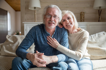 Smiling senior middle aged vloggers couple looking talking at camera recording video blog at home, happy friendly mature old family making videocall sitting on sofa, elderly lifestyle vlog concept
