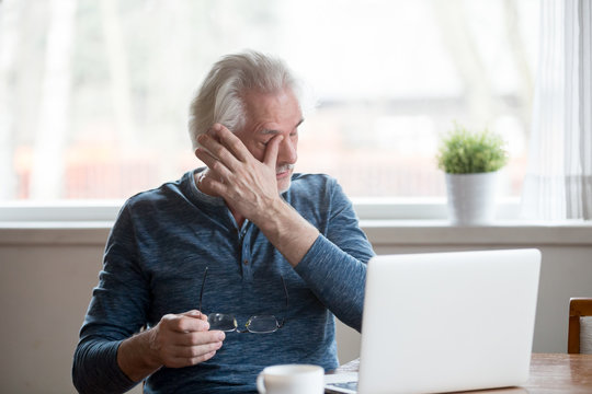 Fatigued mature old man taking off glasses suffering from tired dry irritated eyes after long computer use, senior middle aged male feels eye strain problem or blurry vision working on laptop at home