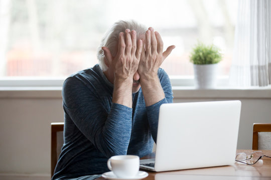 Fatigued senior mature man feels tired from computer rubbing dry irritated eyes to relieve pain or crying frustrated upset, old middle aged male suffering from eyestrain after long laptop use concept