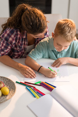 Little boy sketching with his mother at home