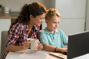 Little boy and his mother using laptop