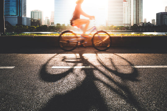 A young women going to work place by her bike in morning.