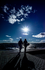 Silhouette of a Couple walking at the Waterfront