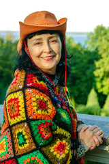 Elegant attractive senior woman in bright multi colored clothes and an orange hat is at nature in autumn park. Vertical.