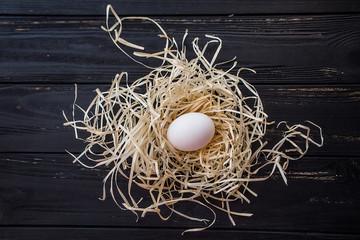 Egg in straw nest on black wooden desc. Top view