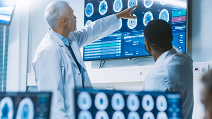 Team of Scientists Work in the Brain Research Laboratory, Discussing Brain Scans Show on Wall TV Monitor. Neurologists / Neuroscientists Surrounded by Monitors Showing CT, MRI Scans.