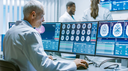 Senior Medical Research Scientist Working with Brain Scans on His Personal Computer. Modern Laboratory Working on Neurophysiology, Science,  Neuropharmacology. Understanding Human Brain.
