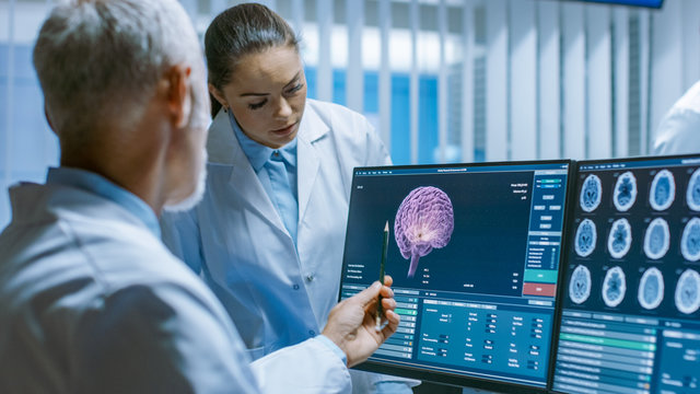Two Medical Scientists in the Brain Research Laboratory Discussing Progress on the Neurophysiology Project Fighting Tumors. Neuroscientists Use Personal Computer with MRI, CT Scans Show Brain Images.