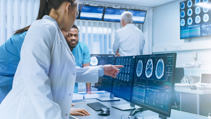 Diverse Team of Medical Scientists Solve Problems and Point at Computer Screens Showing CT, MRI Scans. Neurologists / Neuroscientists Working in Brain Research Laboratory.